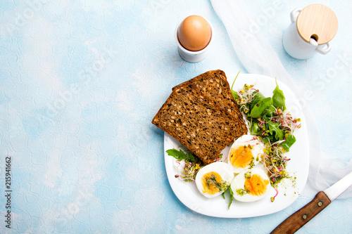 Zdrowe śniadanie: Jajka gotowane na twardo, świeże kiełki, rukola i kromka pełnoziarnistego chleba  na niebieskim tle, miejsce na tekst.