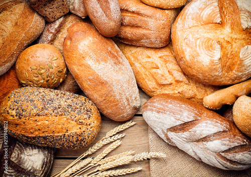 Poster Brood heap of fresh baked bread on wooden background