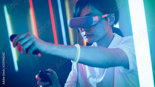 Fotografia East Asian Pro Gamer Wearing Virtual Reality Headset Plays Online Video Game with Joysticks / Controllers