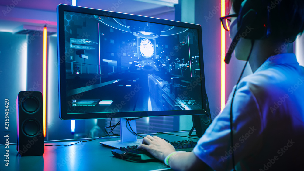 Fototapeta Back View Shot of Professional Gamer Playing in First-Person Shooter Online Video Game on His Personal Computer. He's Talking with His Team Through Headset. Lit by Neon Lights in Retro Arcade Style.