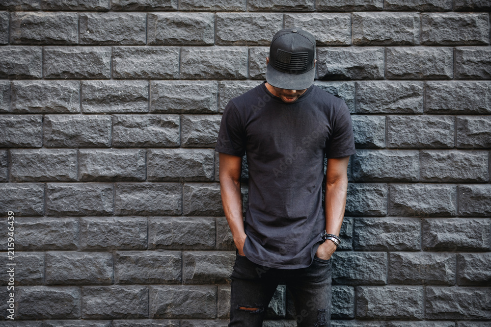 Fototapeta Handsome african american man in blank black t-shirt standing against brick wall