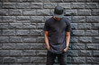 Leinwandbild Motiv Handsome african american man in blank black t-shirt standing against brick wall