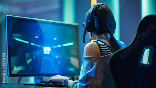 Photo  Shot of the Beautiful Pro Gamer Girl Playing in FPS Video Game on Her Personal Computer, Casual Cute Geek wearing Glasses and Headset