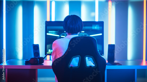 Photo Professional Gamer Playing and Winning in First-Person Shooter Online Video Game on His Personal Computer