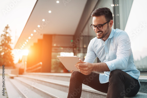 Fotografie, Obraz  Portrait of businessman in glasses holding tablet