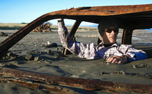 Man Sits In Rusted Car Wreck B...