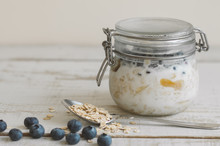 Jar With Ready To Eat Overnight Oats With Coconut Milk And Blueberry On Wooden Table. Breakfast Meal