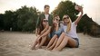 Shot of a group of young friends taking a selfie on the beach. Men and women taking photos sitting on a sand on warm summer evening.