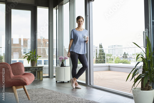 Portrait of woman at home with cup of coffee standing at balcony door
