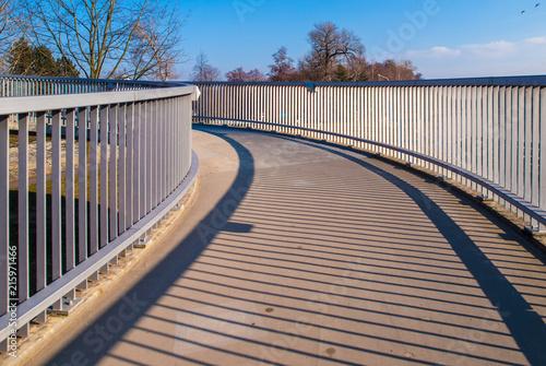 Fényképezés Pedestrian overpass with metal raillings on sunny day.