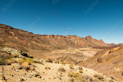 Foto op Aluminium Blauwe jeans View of landscape of Teide National Park on Tenerife, Canarias islands, Spain. Yellow and black sand and distance view of mountains roads and volcano.