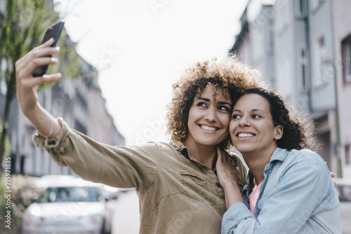 Best friends taking selfies with a smartphone in the city