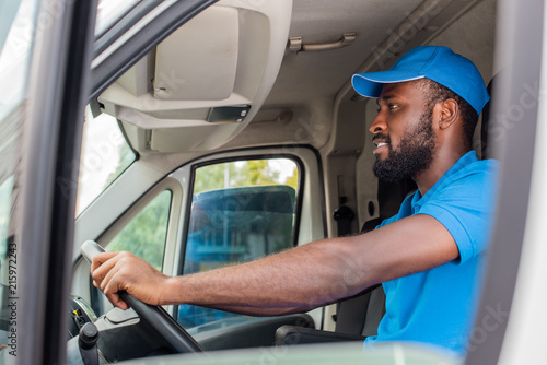 Foto side view of african american delivery man driving van
