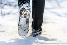 Female Feet In Boots In Snow Walking In Winter