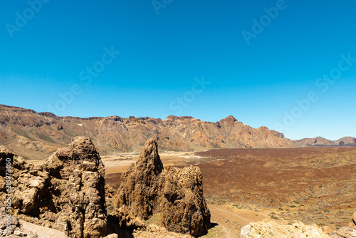Tuinposter Blauw View of landscape of Teide National Park on Tenerife, Canarias islands, Spain. Yellow and black sand and distance view of mountains roads and volcano.
