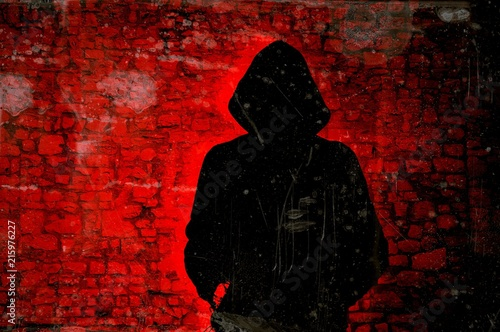 Fotografía  Male figure with hood on red wall background. Hacker concept.