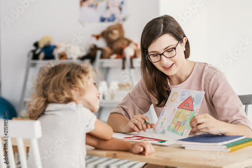 Fotografia  A professional child education therapist having a meeting with a kid in a family support center