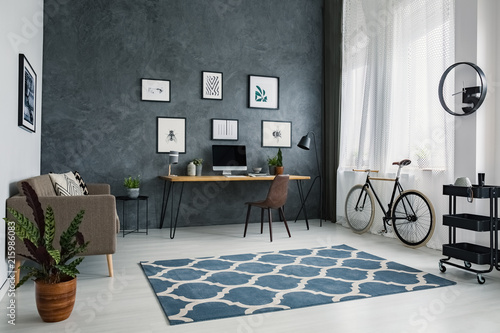 Fotografía  Patterned carpet in bright workspace interior with bicycle next to brown chair at desk