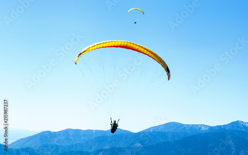 Foto op Canvas Luchtsport Two Paragliders soaring in the sky over the blue mountains
