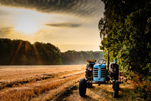 Old Tractor In A Field On A Summer Morning With The Sun Coming Up