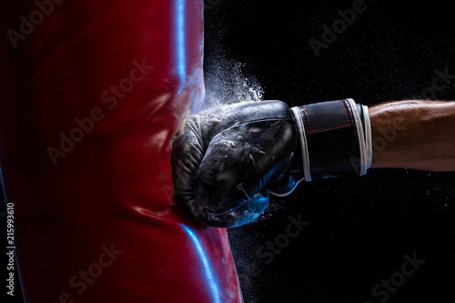 Obraz Close-up hand of boxer at the moment of impact on punching bag over black background - fototapety do salonu