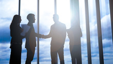 Silhouettes Of Business Partners Handshaking With Man . Handshake Of Business Concept.