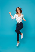 Full Length Portrait Of A Happy Young Housewife Jumping