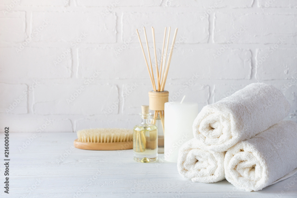 Fototapeta SPA aromatherapy background.  Still life with white towel, bath oil, massage brush and candle.