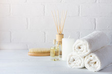 SPA Aromatherapy Background.  Still Life With White Towel, Bath Oil, Massage Brush And Candle.