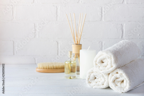 Poster Spa SPA aromatherapy background. Still life with white towel, bath oil, massage brush and candle.
