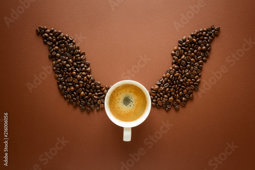 фотография Cup of espresso with wings from coffee beans on brown background