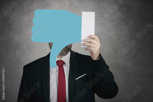 Businessman holding a dislike icon on gray background Wallpaper Mural