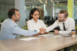 Business people shaking hands at desk in office. Multiethnic businesspeople meeting and sitting with modern blurred interior in background. Agreement concept.