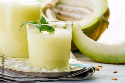 melon smoothie in glass and bottle on white background, summer drink, cocktail