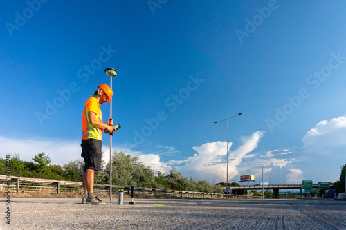 Worker or builder (Surveyor) with GPS on construction site during