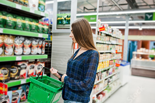 Shopping woman looking at the shelves in the supermarket. Portrait of a young girl in a market store holding green shop basket.