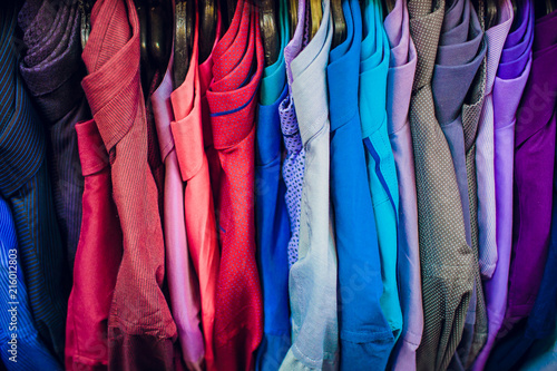 Photo sur Aluminium Aquarelle avec des feuilles tropicales Big clothing store, many rows with hangers with pants and t-shirts, variety sizes