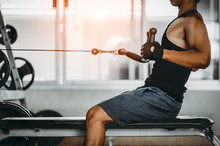 Young Man Making Low Cable Pulley Row Seated.Concept Of Healthy Lifestyle.  Bodybuilder In The Gym.