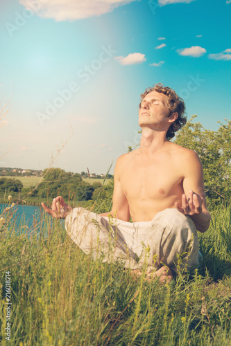 Fotografie, Obraz  A peaceful young man engaged in yoga and meditation in nature.