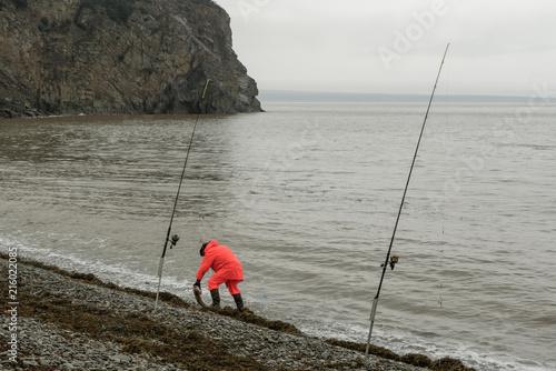 Fotografie, Obraz  lone fisherman in bright orange rain gear on a rainy day at the foggy coast with