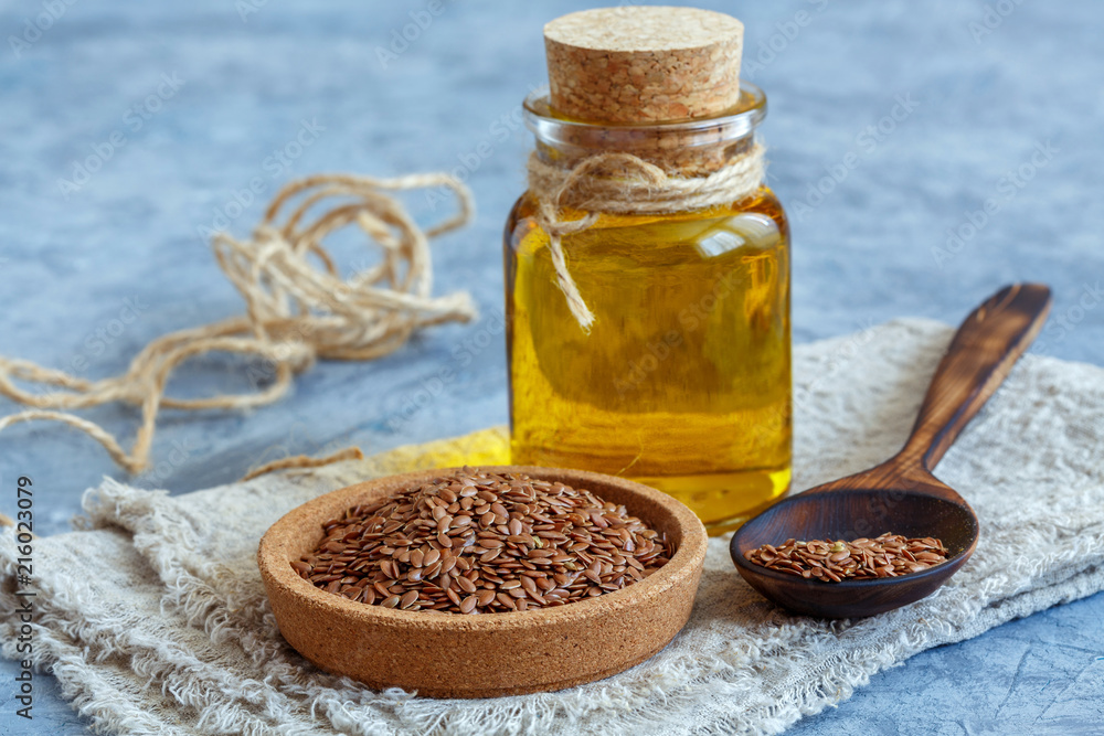 Fototapety, obrazy: Glass bottle with linseed oil and flax seeds.
