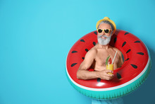 Shirtless Man With Inflatable Ring And Glass Of Cocktail On Color Background