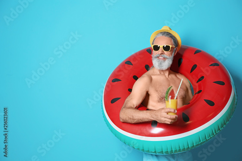 Obraz Shirtless man with inflatable ring and glass of cocktail on color background - fototapety do salonu
