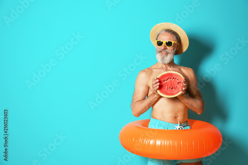 fototapeta na drzwi i meble Shirtless man with inflatable ring and watermelon on color background