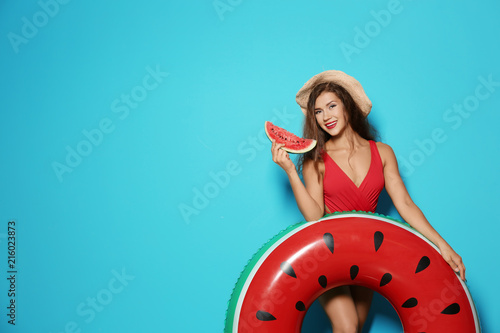 Beautiful young woman with inflatable ring and watermelon on color background