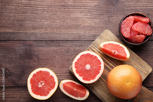 Ripe grapefruits with citting board on brown wooden table