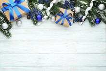 Christmas Fir-tree Branches With Baubles And Gift Boxes On Wooden Table