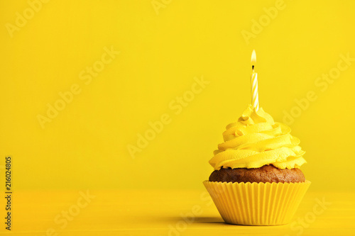 Tasty cupcake with candle on yellow background