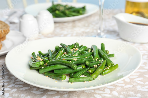 Tasty green beans with sesame seeds served for dinner on table