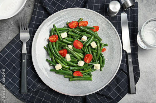 Flat lay composition with plate of fresh green bean salad on table